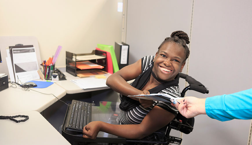 A woman of colour sitting in a wheelchair at her desk with a keyboard positioned in a way that is accessible to her. She is smiling at the camera and accepting some documents from an individual out of frame.