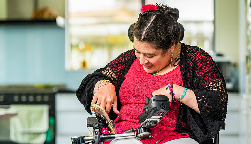 A woman dressed in a red top and black shawl is using her mobile phone. The phone is mounted to her electric wheelchair.