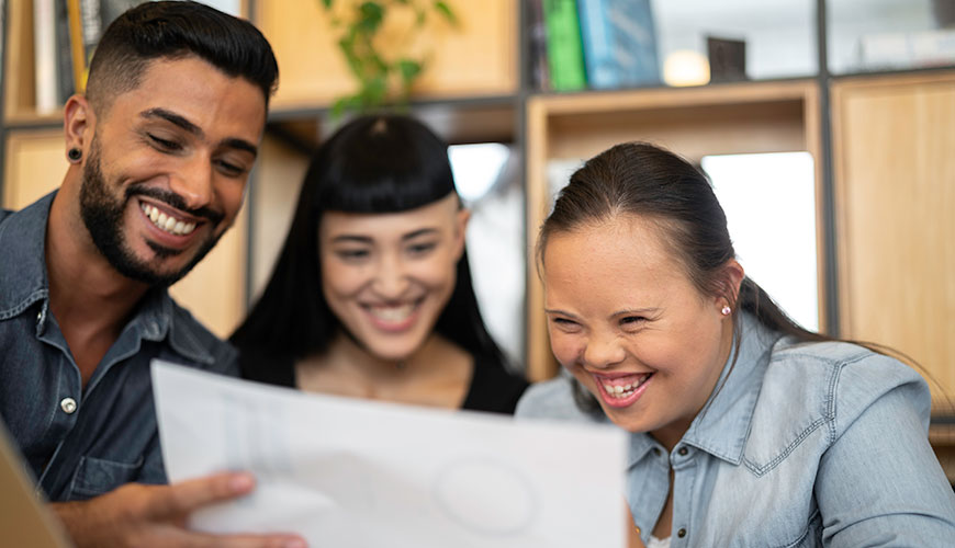 Three people smiling and looking at a work plan together. From left to right: There is a man with dark skin and an earring, a woman with long black hair and another woman also with long dark hair, which is pulled back, who appears to have Down Syndrome.