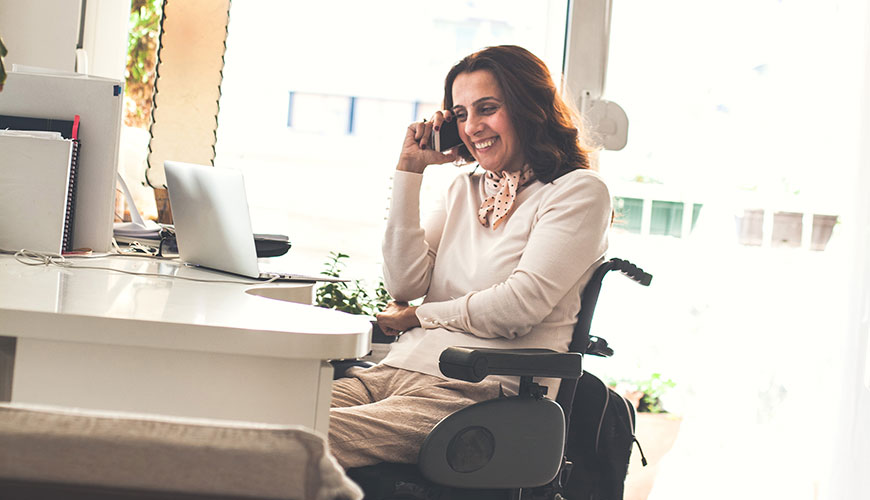 A woman in a wheelchair is smiling while she is on a phone call. She is working from home on her laptop.
