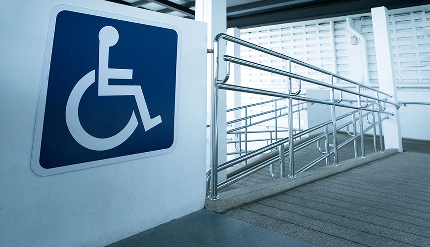 A concrete ramp way with a wheelchair sign at the top.