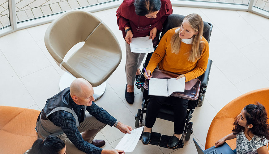 A bird's eye view of a group of people sitting in a circle with laptops and notebooks. Some people are on couches, and others are on chairs. One woman is in a wheelchair.