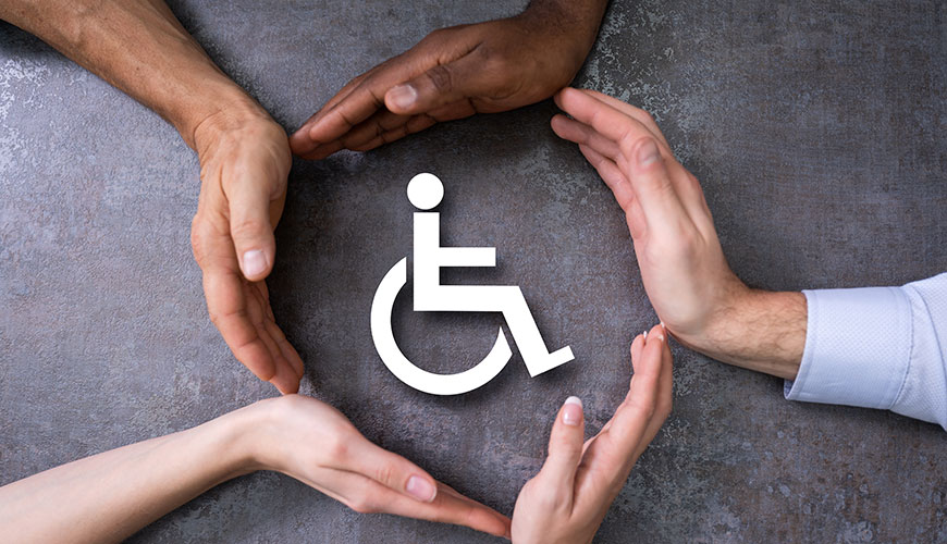 A group of hands, all with different coloured skin tones, create a circle around a sign for disability.