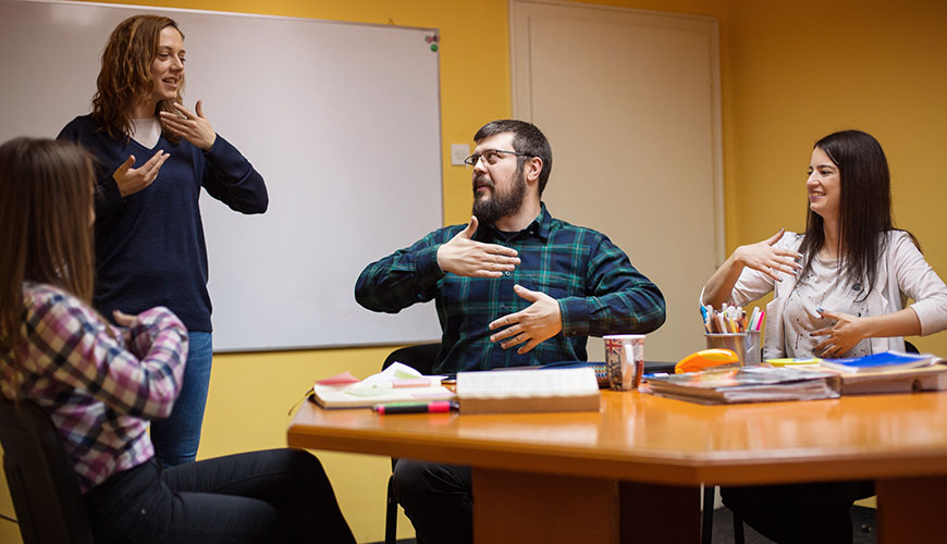 A group of men and women are in a staff meeting. They are all communicating  together through sign language.