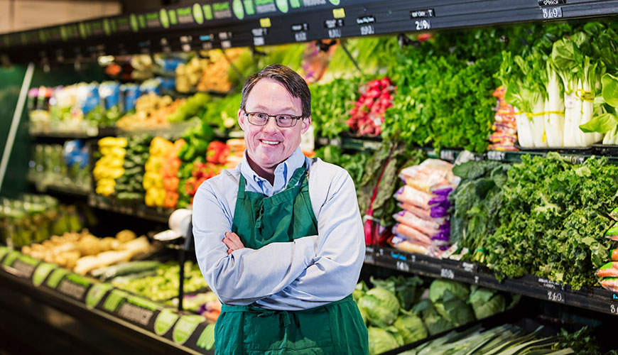 A man working in a grocery store. He wears a buttoned up shirt and a green apron. He appears to have Down Syndrome.