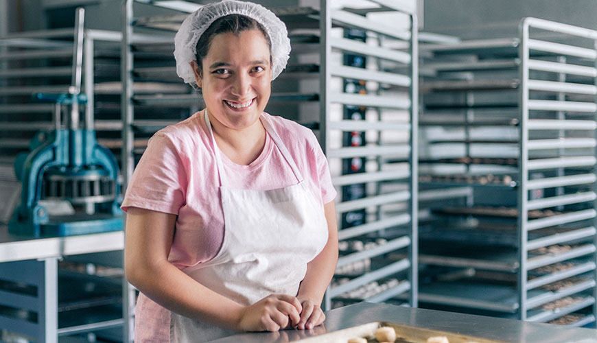 A woman wearing an apron and hairnet is smiling in an industrial bakery kitchen. She has a tray of pastries in front of her.