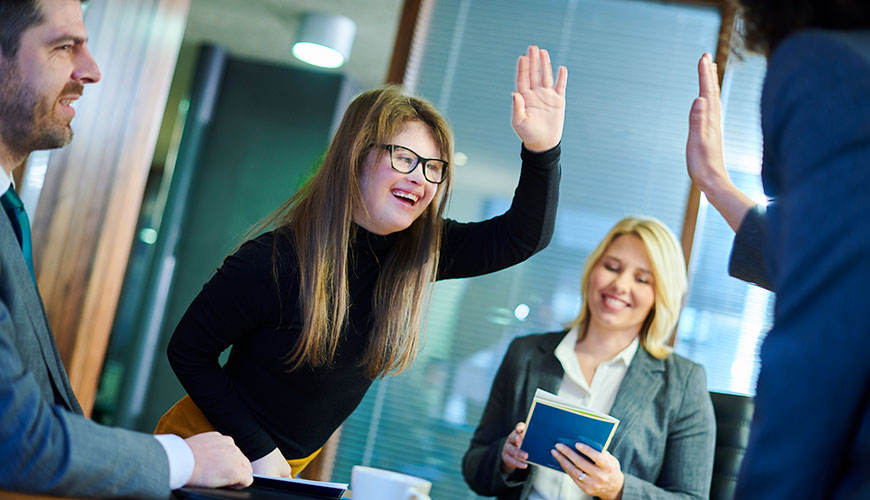 Two colleagues are raising hands for a high five. One is partially out of frame and the other is a young woman with long blonde hair and Down Syndrome.  A male colleague is smiling and  a woman is also smiling and looking down at a book.