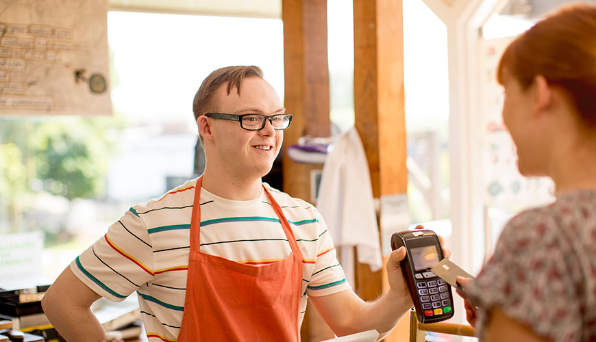 A young man with Down Syndrome is holding up an EFTPOS machine to a customer. He is working in a café.